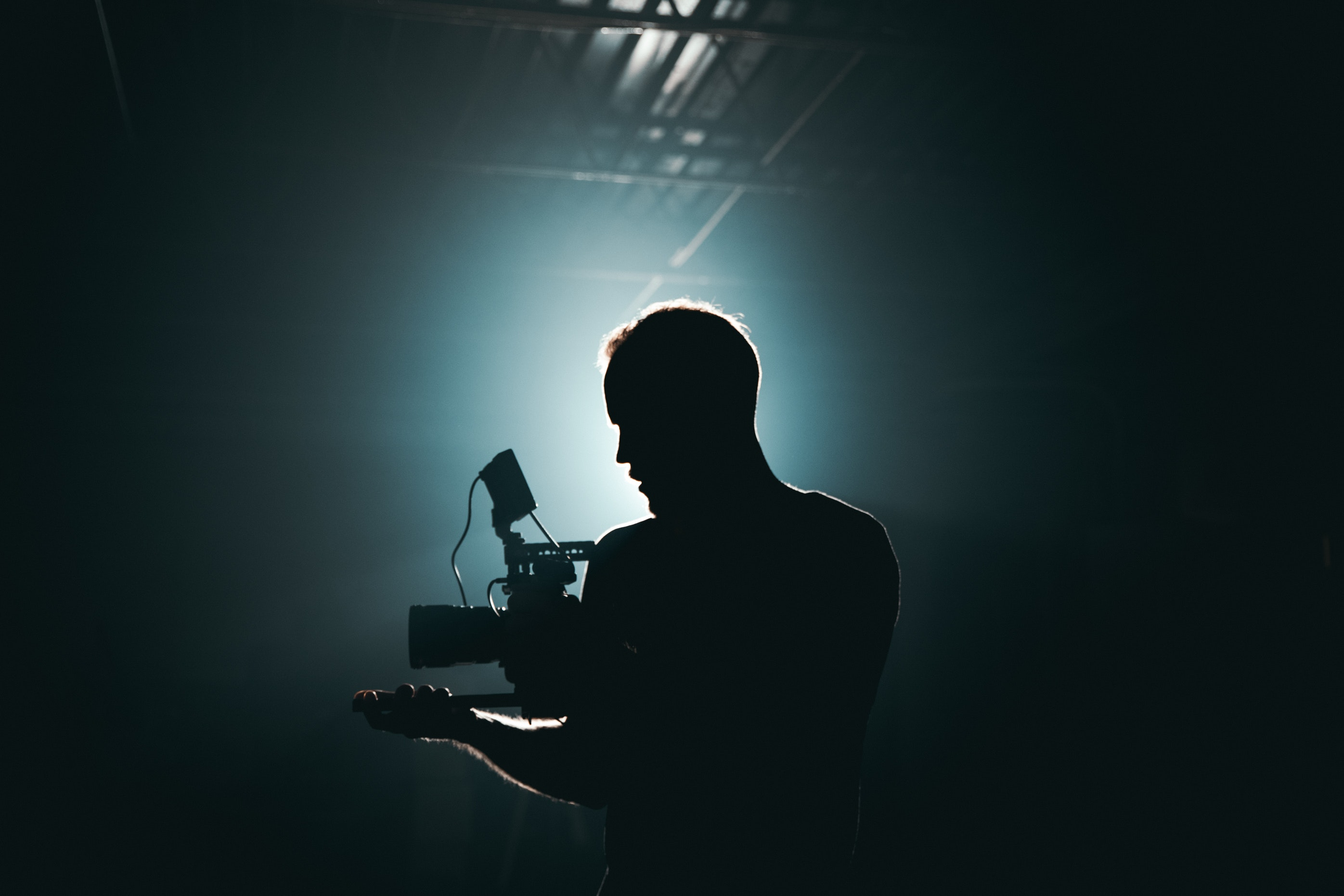 Wewa Films | Silhouette of man in dark room holding a video camera